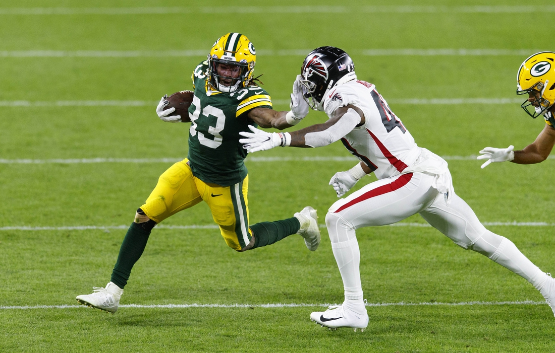 Oct 5, 2020; Green Bay, Wisconsin, USA;  Green Bay Packers running back Aaron Jones (33) rushes with the football during the third quarter against the Atlanta Falcons at Lambeau Field. Mandatory Credit: Jeff Hanisch-USA TODAY Sports