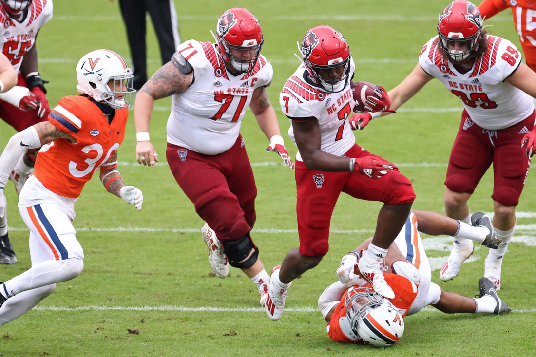 Oct 10, 2020; Charlottesville, Virginia, USA; North Carolina State Wolfpack running back Zonovan Knight (7) leaps over Virginia Cavaliers linebacker Charles Snowden (11) while carrying the ball in the fourth quarter at Scott Stadium. Mandatory Credit: Geoff Burke-USA TODAY Sports