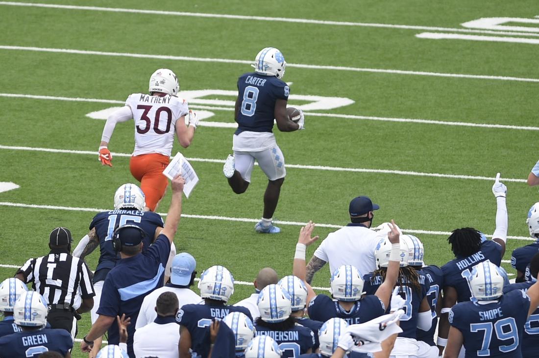 Oct 10, 2020; Chapel Hill, North Carolina, USA; North Carolina Tar Heels running back Michael Carter (8) scores a touchdown as Virginia Tech Hokies defensive back Tyler Matheny (30) defends in the fourth quarter at Kenan Memorial Stadium. Mandatory Credit: Bob Donnan-USA TODAY Sports