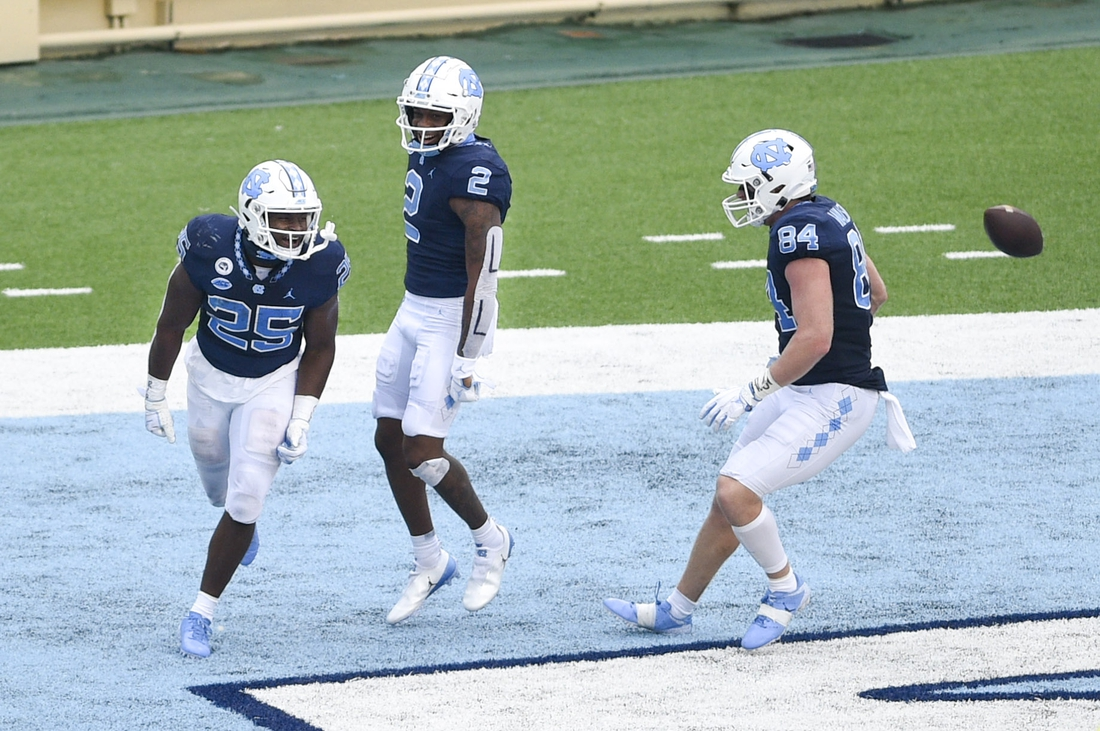 Oct 10, 2020; Chapel Hill, North Carolina, USA; North Carolina Tar Heels running back Javonte Williams (25) celebrates with wide receiver Dyami Brown (2) and tight end Garrett Walston (84) after scoring a touchdown in the first quarter at Kenan Memorial Stadium. Mandatory Credit: Bob Donnan-USA TODAY Sports