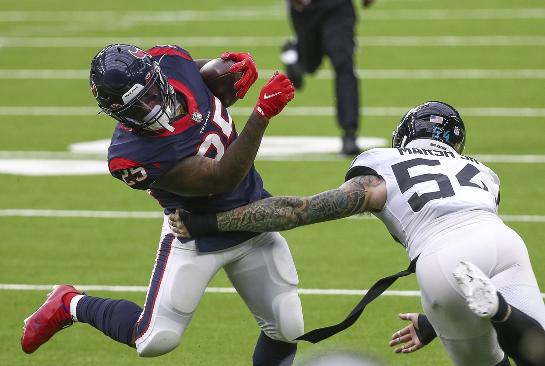 Oct 11, 2020; Houston, Texas, USA; Houston Texans running back Duke Johnson (25) runs with the ball as Jacksonville Jaguars linebacker Cassius Marsh (54) defends during the fourth quarter at NRG Stadium. Mandatory Credit: Troy Taormina-USA TODAY Sports
