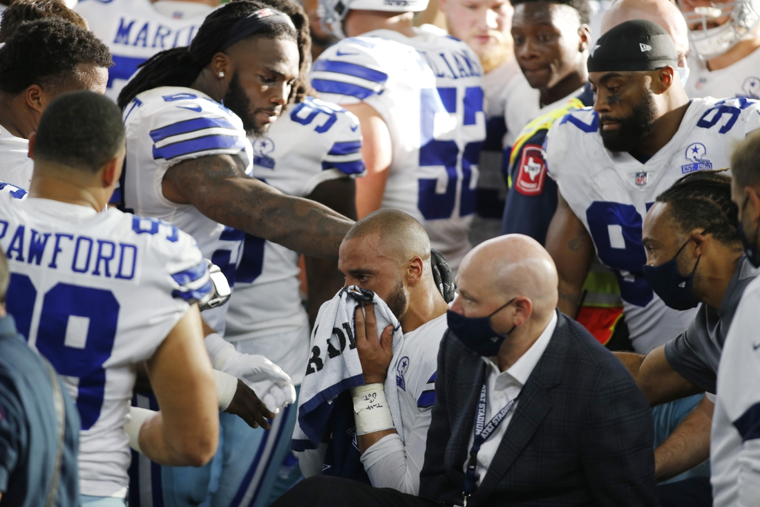 Oct 11, 2020; Arlington, Texas, USA; Dallas Cowboys quarterback Dak Prescott (4) is comforted by his teammates after an injury in the third quarter against the New York Giants at AT&T Stadium. Mandatory Credit: Tim Heitman-USA TODAY Sports