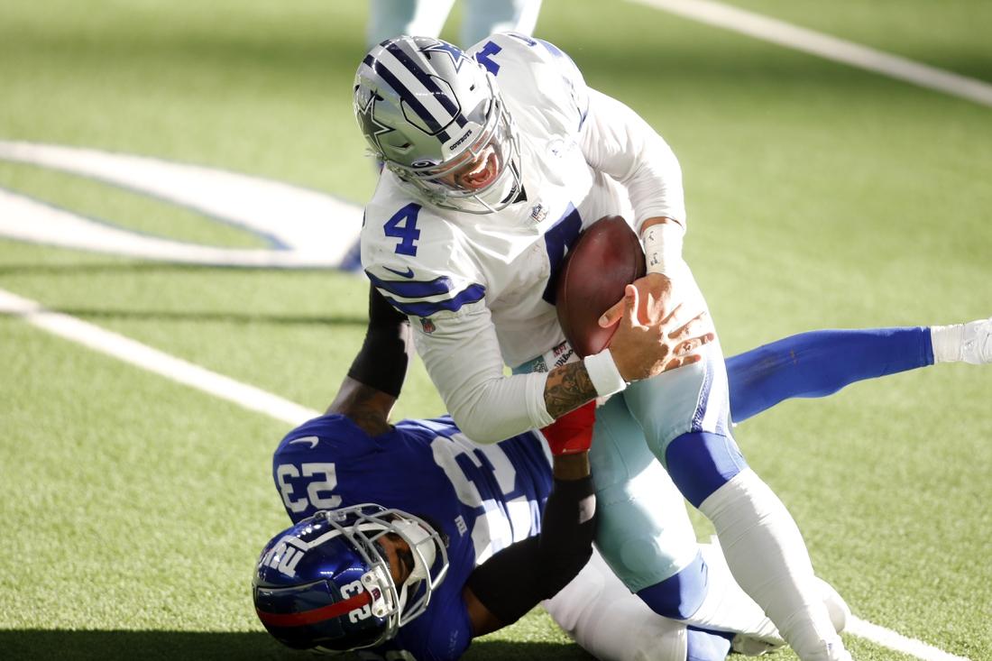 Oct 11, 2020; Arlington, Texas, USA; Dallas Cowboys quarterback Dak Prescott (4) is tackled and injured by New York Giants cornerback Logan Ryan (23) in the third quarter at AT&T Stadium. Mandatory Credit: Tim Heitman-USA TODAY Sports