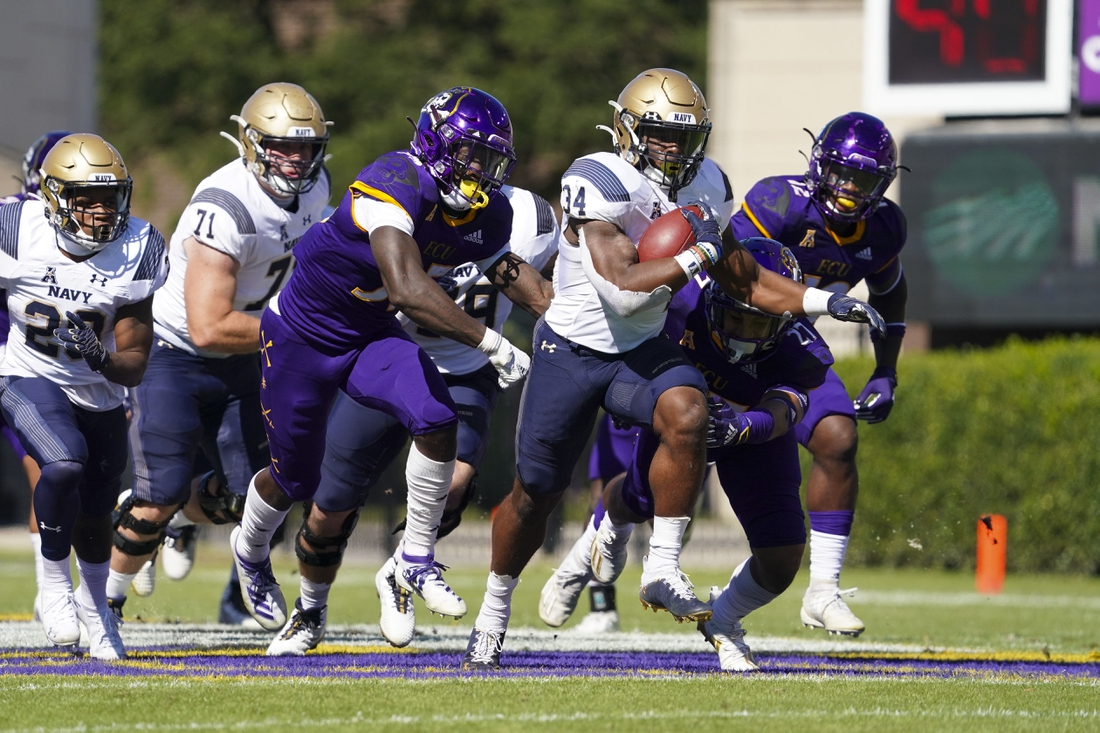 Oct 17, 2020; Greenville, North Carolina, USA;  Navy Midshipmen fullback Jamale Carothers (34) runs with the ball past defensive back East Carolina Pirates Jireh Wilson (35) and defensive back Shawn Dourseau (27) during the first half at Dowdy-Ficklen Stadium. Mandatory Credit: James Guillory-USA TODAY Sports