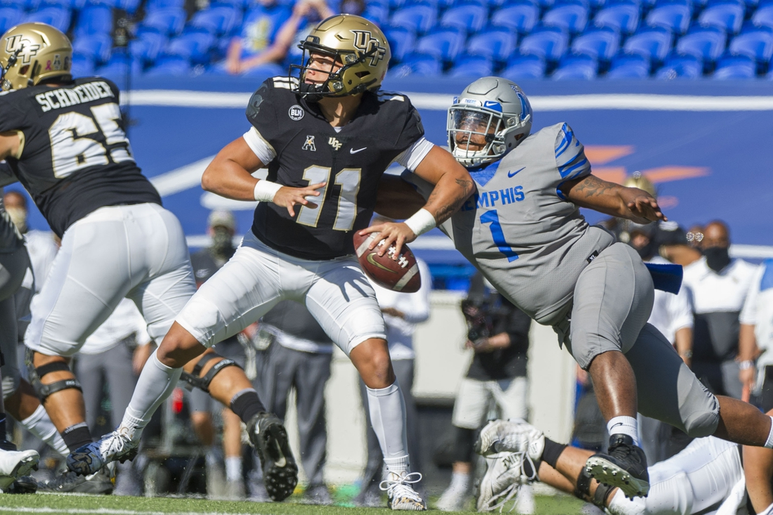 Oct 17, 2020; Memphis, Tennessee, USA; UCF Knights quarterback Dillon Gabriel (11) is pressured by Memphis Tigers defensive lineman O'Bryan Goodson (1) during the first half  at Liberty Bowl Memorial Stadium. Mandatory Credit: Justin Ford-USA TODAY Sports