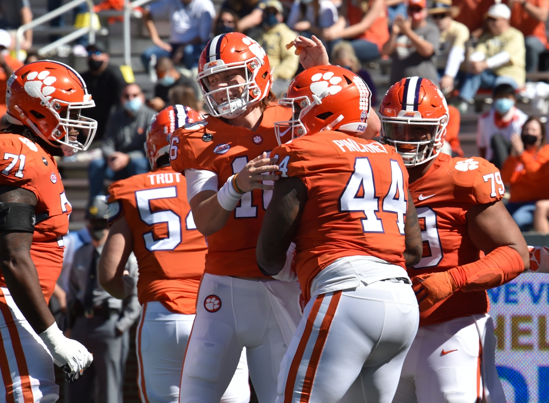 Oct 17, 2020; Atlanta, GA, USA;  Clemson Tigers defensive tackle Nyles Pinckney (44) celebrates with Clemson Tigers quarterback Trevor Lawrence (16) after he scored a touchdown during the first half of an NCAA college football game at Bobby Dodd Stadium. Mandatory Credit: Hyosub Shin/Pool Photo-USA TODAY Sports