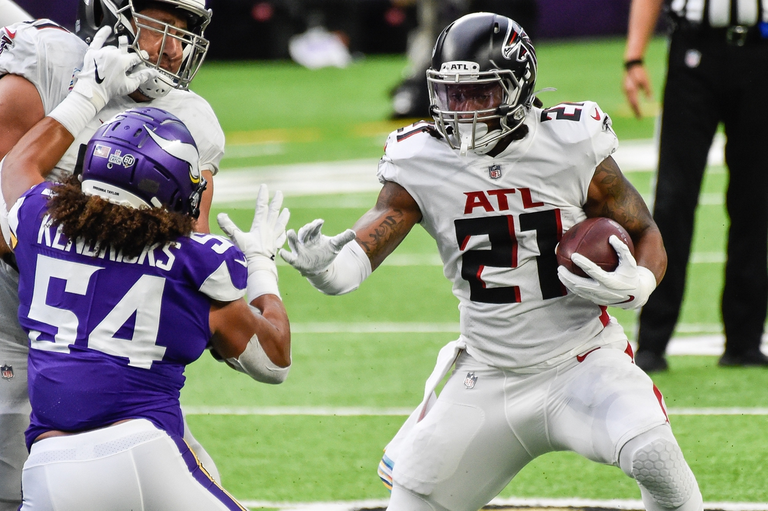 Oct 18, 2020; Minneapolis, Minnesota, USA; Atlanta Falcons running back Todd Gurley (21) runs the ball as Minnesota Vikings middle linebacker Eric Kendricks (54) looks on during the first quarter at U.S. Bank Stadium. Mandatory Credit: Jeffrey Becker-USA TODAY Sports