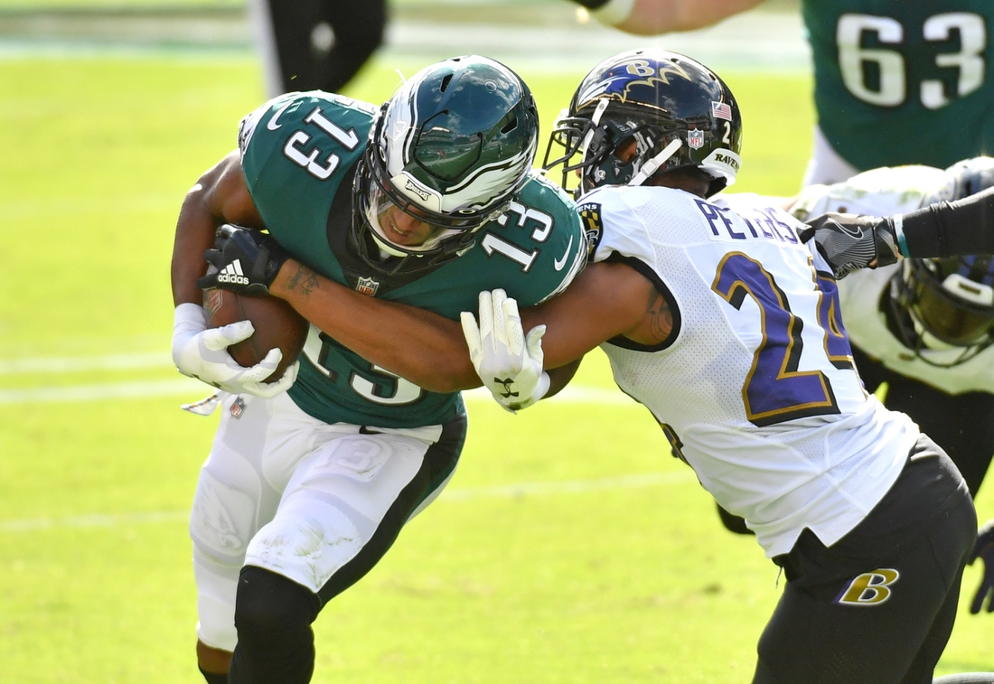 Oct 18, 2020; Philadelphia, Pennsylvania, USA; Philadelphia Eagles wide receiver Travis Fulgham (13) is tackled by Baltimore Ravens cornerback Marcus Peters (24) during the second quarter at Lincoln Financial Field. Mandatory Credit: Eric Hartline-USA TODAY Sports