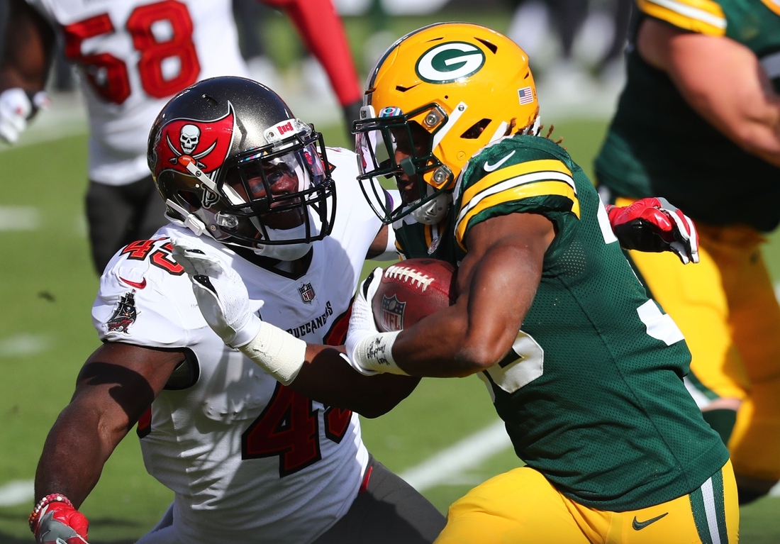 Oct 18, 2020; Tampa, Florida, USA; Green Bay Packers running back Aaron Jones (33) runs against Tampa Bay Buccaneers defensive back Ross Cockrell (43) during the first quarter of a NFL game at Raymond James Stadium. Mandatory Credit: Kim Klement-USA TODAY Sports