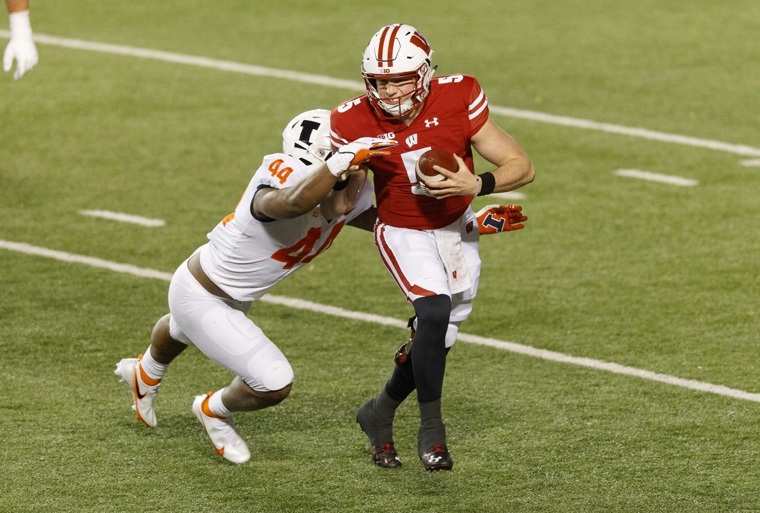 Oct 23, 2020; Madison, Wisconsin, USA;  Wisconsin Badgers quarterback Graham Mertz (5) is tackled by Illinois Fighting Illini linebacker Tarique Barnes (44) during the second quarter at Camp Randall Stadium. Mandatory Credit: Jeff Hanisch-USA TODAY Sports
