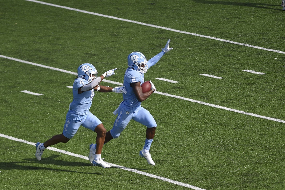 Oct 24, 2020; Chapel Hill, North Carolina, USA; North Carolina Tar Heels defensive back Don Chapman (2) celebrates with defensive back Trey Morrison (4) after intercepting a pass in the end zone intended in the second quarter at Kenan Memorial Stadium. Mandatory Credit: Bob Donnan-USA TODAY Sports