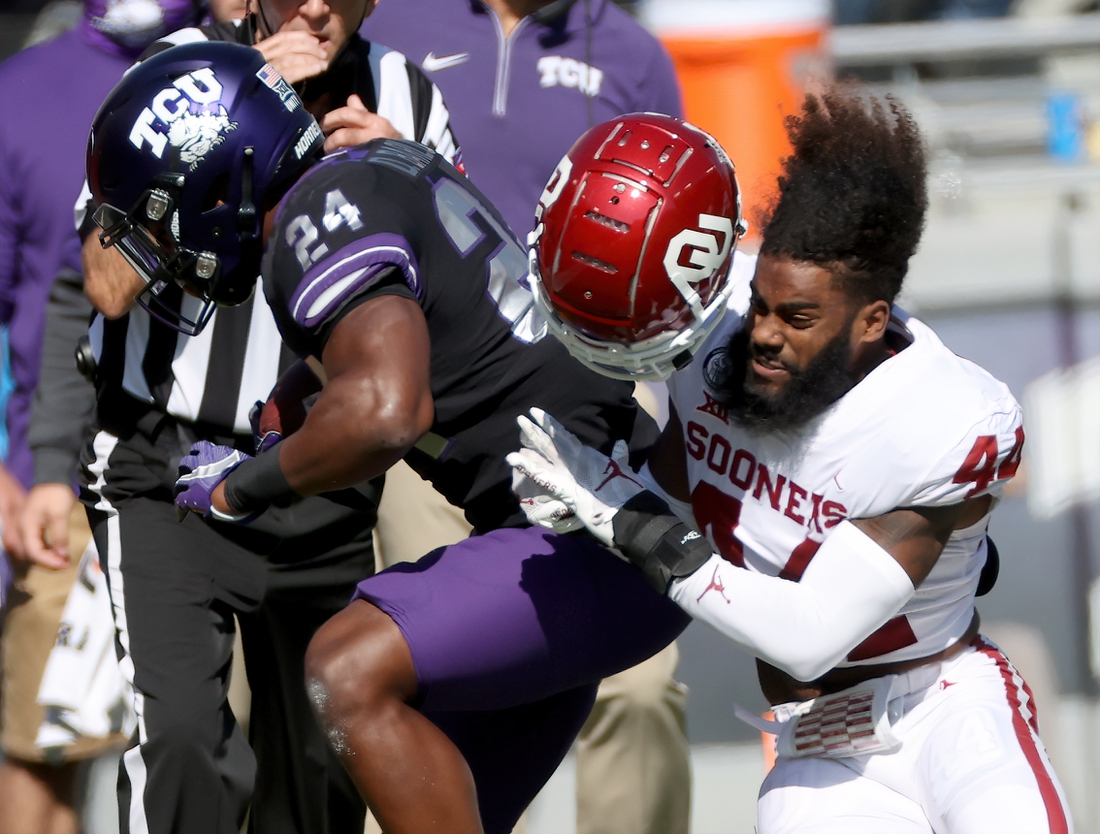Oct 24, 2020; Fort Worth, Texas, USA; Oklahoma Sooners defensive back Brendan Radley-Hiles (44) tackles TCU Horned Frogs running back Darwin Barlow (24) during the first half at Amon G. Carter Stadium. Mandatory Credit: Kevin Jairaj-USA TODAY Sports