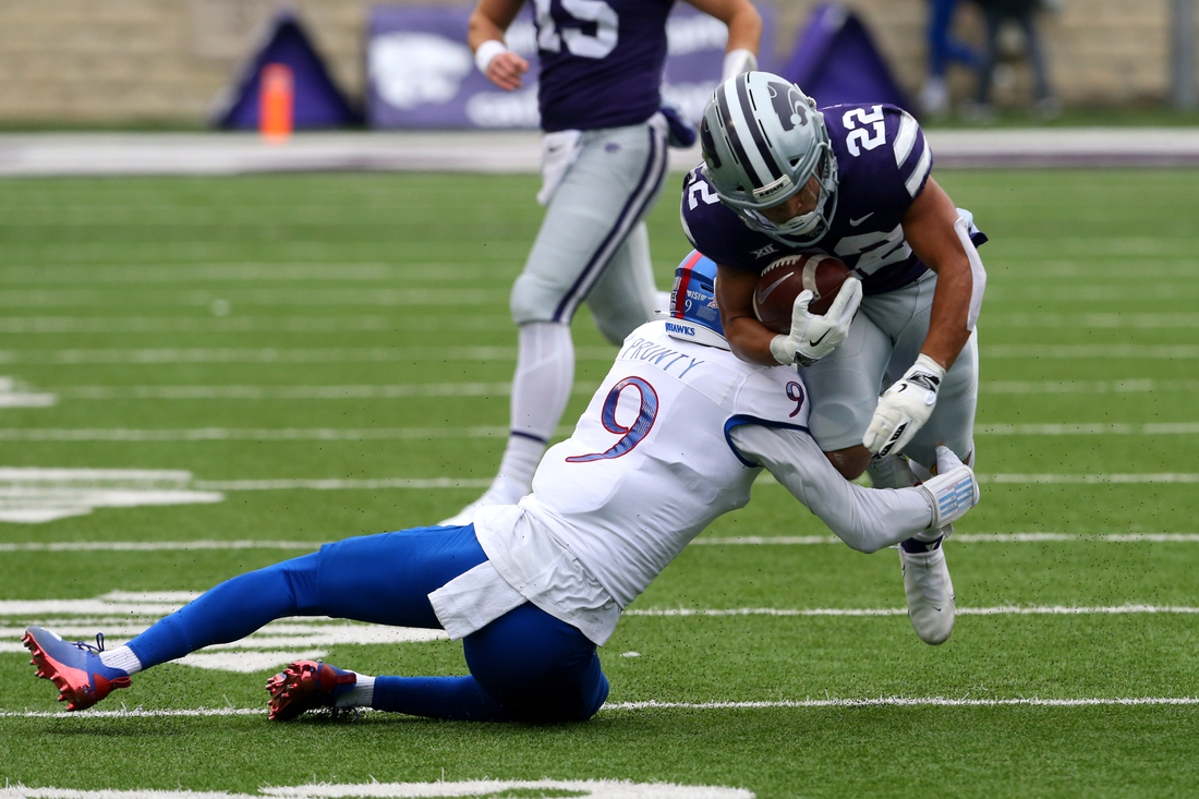 Oct 24, 2020; Manhattan, Kansas, USA; Kansas State Wildcats running back Deuce Vaughn (22) is tackled by a Kansas Jayhawks defender during the first half of a game at Bill Snyder Family Football Stadium. Mandatory Credit: Scott Sewell-USA TODAY Sports