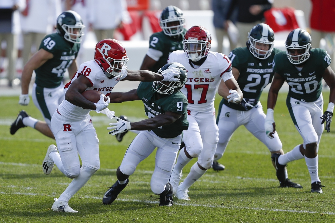 Oct 24, 2020; East Lansing, Michigan, USA; Rutgers Scarlet Knights wide receiver Bo Melton (18) stiff arms Michigan State Spartans safety Dominique Long (9) during the second quarter at Spartan Stadium. Mandatory Credit: Raj Mehta-USA TODAY Sports