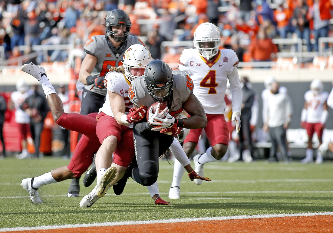 Oct 24, 2020; Stillwater, Oklahoma, USA;  Oklahoma State Cowboys player Jelani Woods (89) scores a touchdown as Iowa State Cyclones player Mike Rose defends in the first quarter at Boone Pickens Stadium. Mandatory Credit: Sarah Phipps-USA TODAY Sports