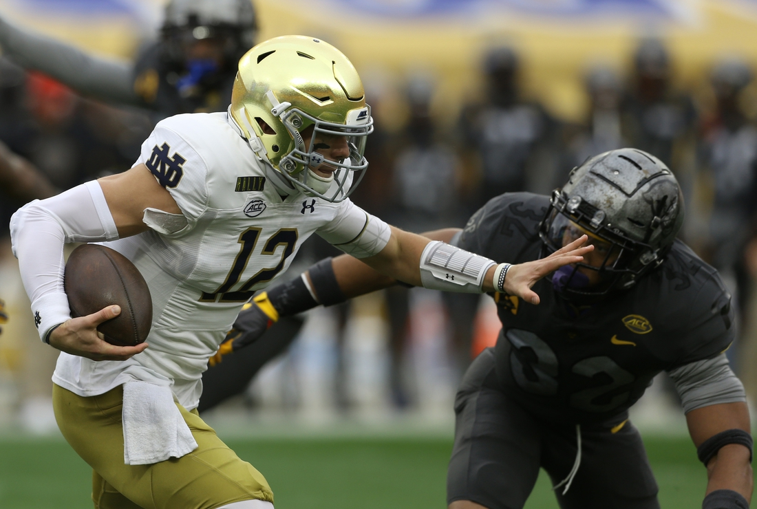 Oct 24, 2020; Pittsburgh, Pennsylvania, USA;  Notre Dame Fighting Irish quarterback Ian Book (12) rushes the ball as Pittsburgh Panthers linebacker SirVocea Dennis (32) defends during the first quarter at Heinz Field. Mandatory Credit: Charles LeClaire-USA TODAY Sports