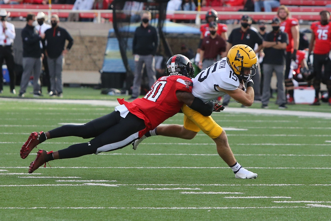 Oct 24, 2020; Lubbock, Texas, USA;  West Virginia Mountaineers wide receiver Reese Smith (15) is tackled by Texas Tech Red Raiders defensive back Cam White (10) in the first half at Jones AT&T Stadium. Mandatory Credit: Michael C. Johnson-USA TODAY Sports
