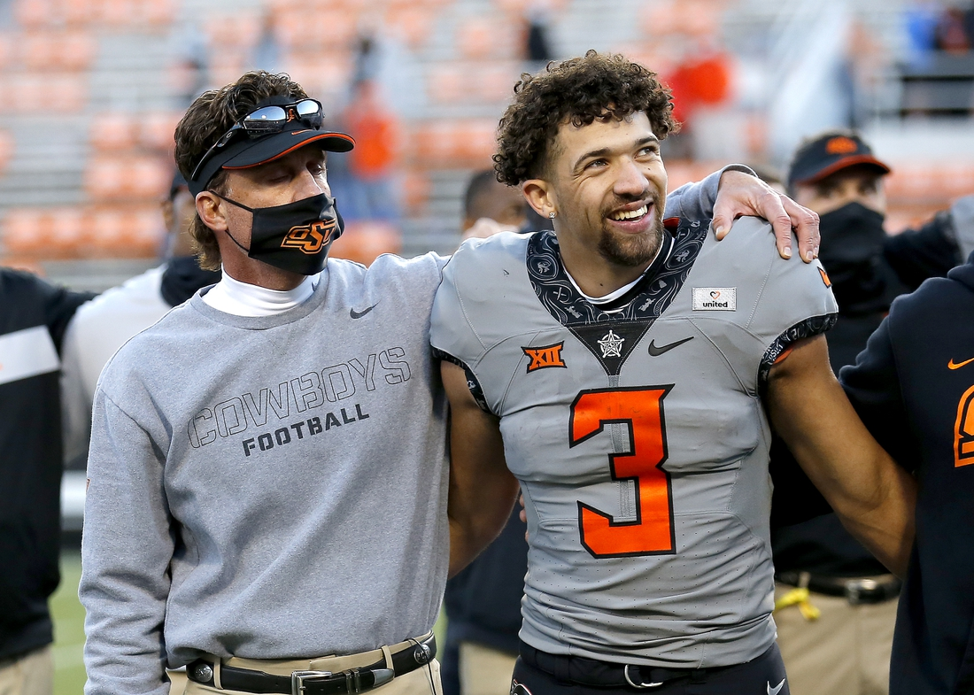 Oct 24, 2020; Stillwater, Oklahoma, USA; Oklahoma State head coach Mike Gundy sings the alma mater with Oklahoma State Cowboys quarterback Spencer Sanders (3) after beating Iowa State 24-21.at Boone Pickens Stadium. Mandatory Credit: Sarah Phipps-USA TODAY Sports