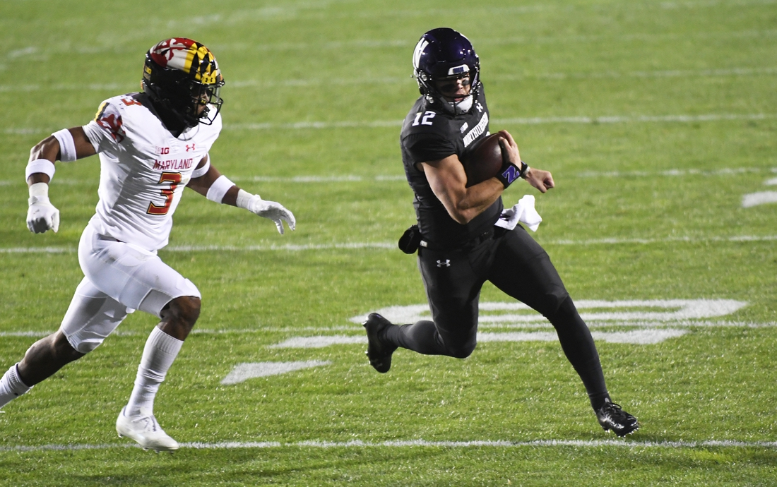 Oct 24, 2020; Evanston, Illinois, USA; Northwestern Wildcats quarterback Peyton Ramsey (12) runs for a touchdown as Maryland Terrapins defensive back Nick Cross (3) tries to tackle him during the first half at Ryan Field. Mandatory Credit: David Banks-USA TODAY Sports