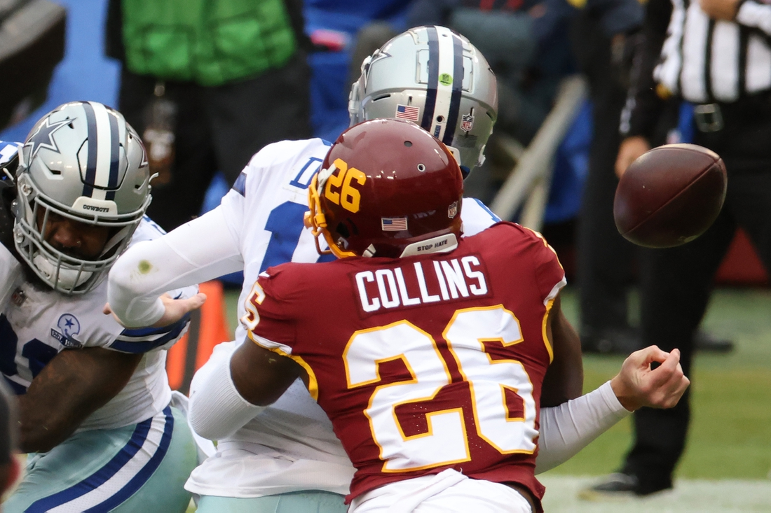 Oct 25, 2020; Landover, Maryland, USA; Dallas Cowboys quarterback Andy Dalton (14) fumbles the ball on a hit by Washington Football Team strong safety Landon Collins (26) in the first quarter at FedExField. Mandatory Credit: Geoff Burke-USA TODAY Sports