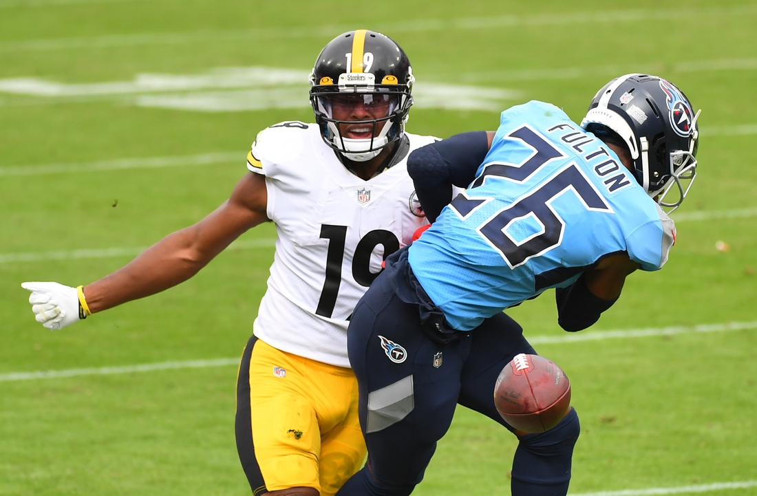 Oct 25, 2020; Nashville, Tennessee, USA; Tennessee Titans cornerback Kristian Fulton (26) breaks up a pass intended for Pittsburgh Steelers wide receiver JuJu Smith-Schuster (19) during the first half at Nissan Stadium. Mandatory Credit: Christopher Hanewinckel-USA TODAY Sports