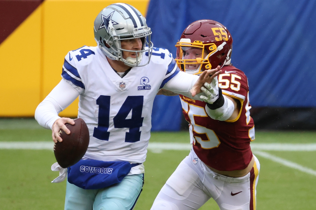 Oct 25, 2020; Landover, Maryland, USA; Dallas Cowboys quarterback Andy Dalton (14) scrambles from Washington Football Team inside linebacker Cole Holcomb (55) in the second quarter at FedExField. Mandatory Credit: Geoff Burke-USA TODAY Sports