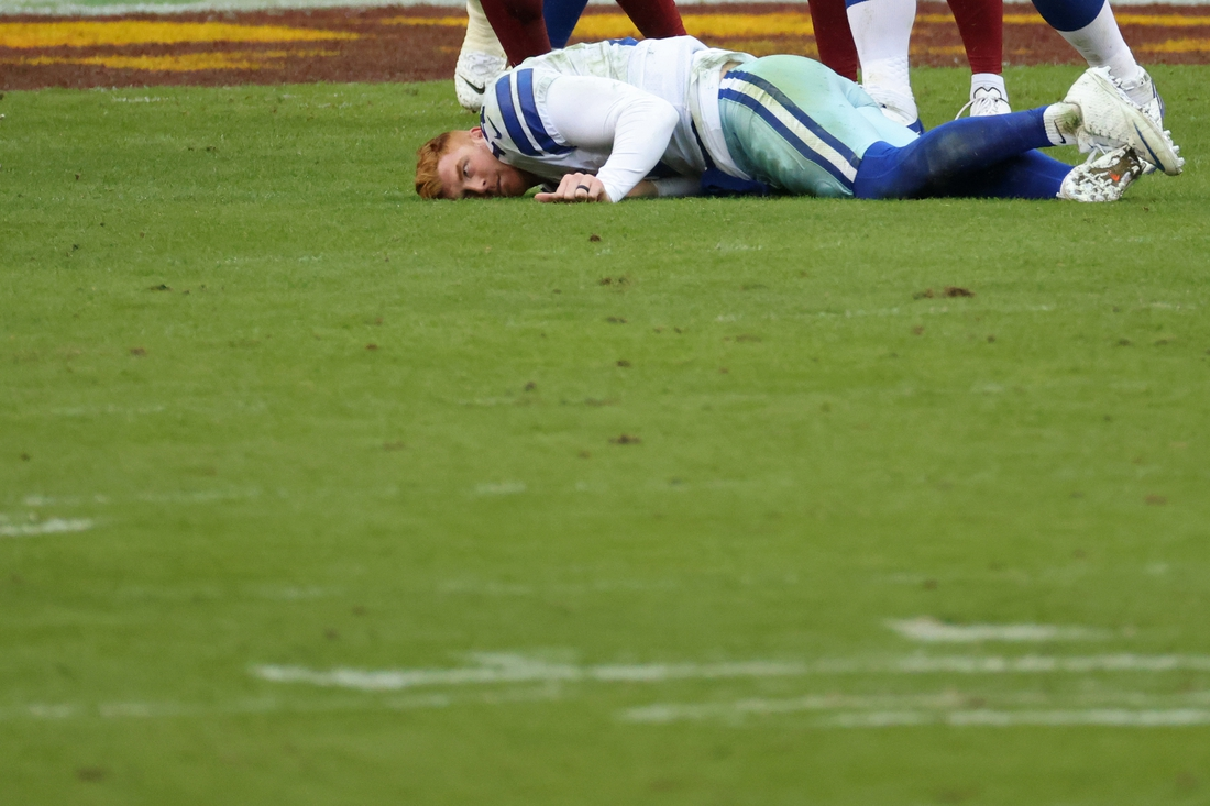 Oct 25, 2020; Landover, Maryland, USA; Dallas Cowboys quarterback Andy Dalton (14) lies on the field after being hit by Washington Football Team inside linebacker Jon Bostic (not pictured) and knocked out of the game in the third quarter at FedExField. Mandatory Credit: Geoff Burke-USA TODAY Sports
