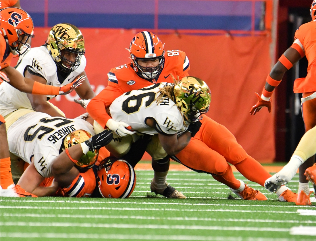 Oct 31, 2020; Syracuse, New York, USA; Wake Forest Demon Deacons running back Christian Beal-Smith (26) is tackled by Syracuse Orange defensive lineman Josh Black (85) in the first quarter at the Carrier Dome. Mandatory Credit: Mark Konezny-USA TODAY Sports