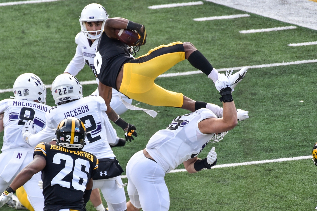 Oct 31, 2020; Iowa City, Iowa, USA; Iowa Hawkeyes wide receiver Ihmir Smith-Marsette (6) is thrown into the air by Northwestern Wildcats linebacker Erik Mueller (35) during the second quarter at Kinnick Stadium. Mandatory Credit: Jeffrey Becker-USA TODAY Sports