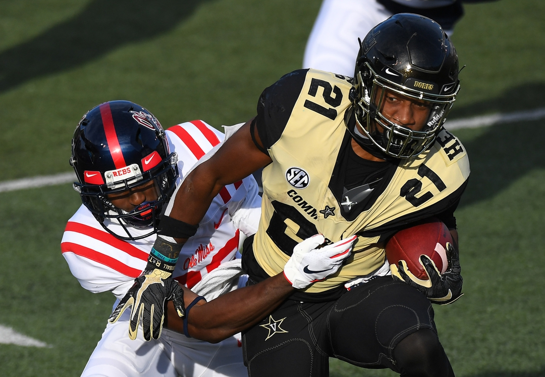 Oct 31, 2020; Nashville, Tennessee, USA; Vanderbilt Commodores running back Keyon Henry-Brooks (21) fights for extra yards as he is tackled by Mississippi Rebels defensive back Keidron Smith (20) during the first half at Vanderbilt Stadium. Mandatory Credit: Christopher Hanewinckel-USA TODAY Sports