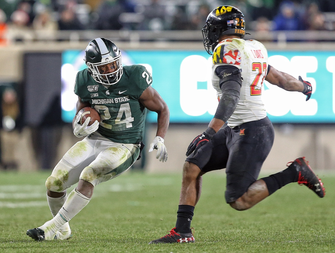 Nov 30, 2019; East Lansing, MI, USA; Michigan State Spartans running back Elijah Collins (24) runs the ball in front of Maryland Terrapins defensive lineman Bryce Brand (27) during the second half a game at Spartan Stadium. Mandatory Credit: Mike Carter-USA TODAY Sports