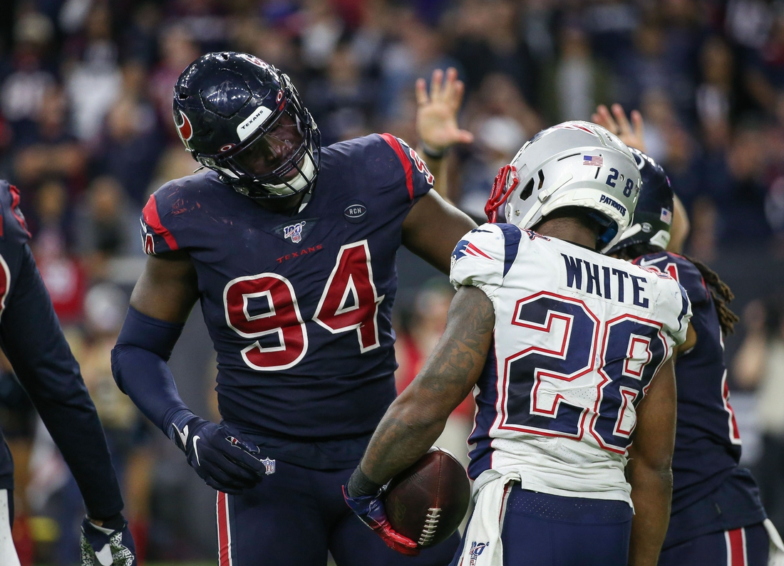 Dec 1, 2019; Houston, TX, USA; Houston Texans defensive end Charles Omenihu (94) and New England Patriots running back James White (28) react during the game at NRG Stadium. Mandatory Credit: Troy Taormina-USA TODAY Sports