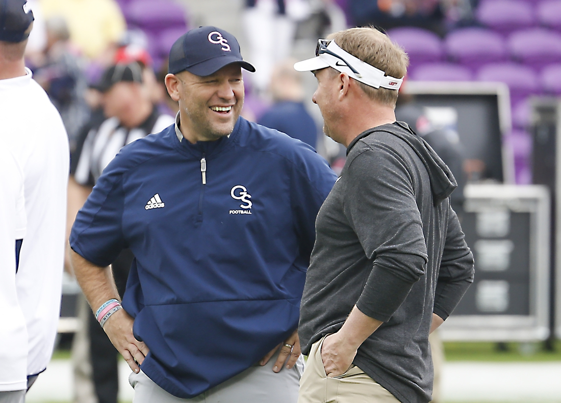 Dec 21, 2019; Orlando, Florida, USA; Liberty Flames head coach Hugh Freeze (right) and Georgia Southern Eagles head coach Chad Lunsford talk before the game at Exploria Stadium. Mandatory Credit: Reinhold Matay-USA TODAY Sports