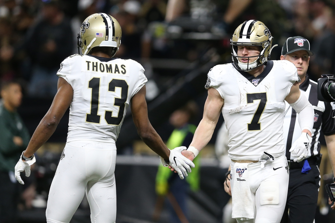 Jan 5, 2020; New Orleans, Louisiana, USA; New Orleans Saints quarterback Taysom Hill (7) celebrates with wide receiver Michael Thomas (13) after scoring a touchdown against the Minnesota Vikings during the fourth quarter of a NFC Wild Card playoff football game at the Mercedes-Benz Superdome. Mandatory Credit: Chuck Cook -USA TODAY Sports