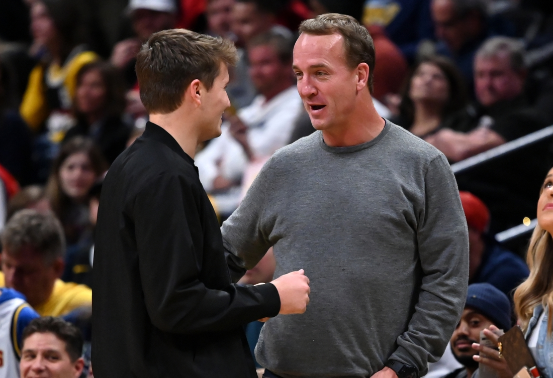 Mar 1, 2020; Denver, Colorado, USA; Denver Broncos quarterback Drew Lock (left) talks with retired NFL quarterback Peyton Manning (right) during the game between the Toronto Raptors against the Denver Nuggets at the Pepsi Center. Mandatory Credit: Ron Chenoy-USA TODAY Sports