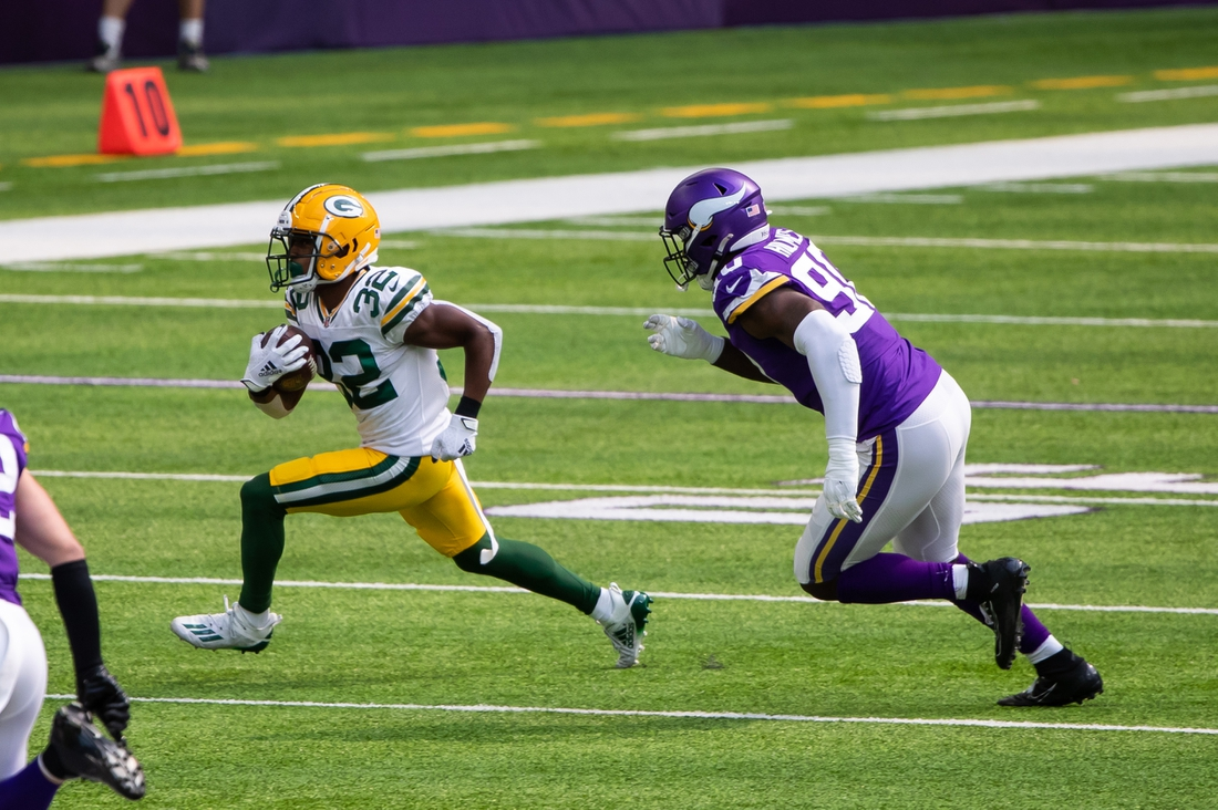 Sep 13, 2020; Minneapolis, Minnesota, USA; Green Bay Packers running back Tyler Ervin (32) runs with the ball in the first quarter against the Minnesota Vikings defensive lineman Jalyn Holmes (90) at U.S. Bank Stadium. Mandatory Credit: Brad Rempel-USA TODAY Sports