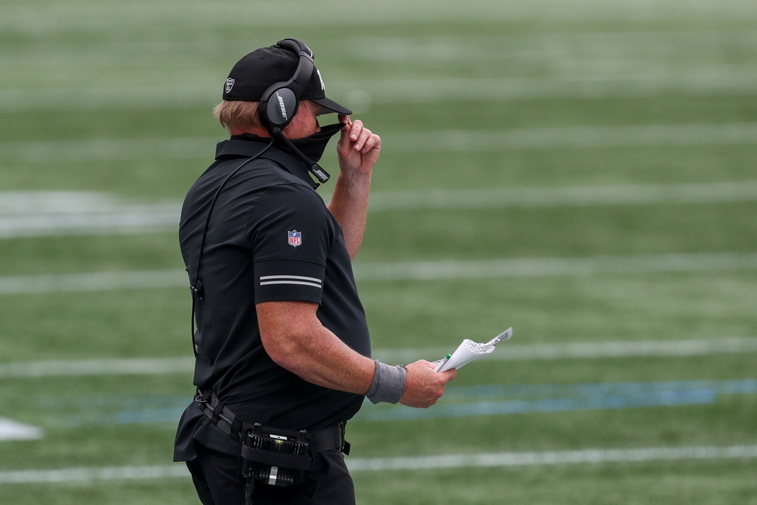 Sep 27, 2020; Foxborough, Massachusetts, USA; Las Vegas Raiders head coach Jon Gruden adjusts his face covering during the second half against the New England Patriots at Gillette Stadium. Mandatory Credit: Paul Rutherford-USA TODAY Sports