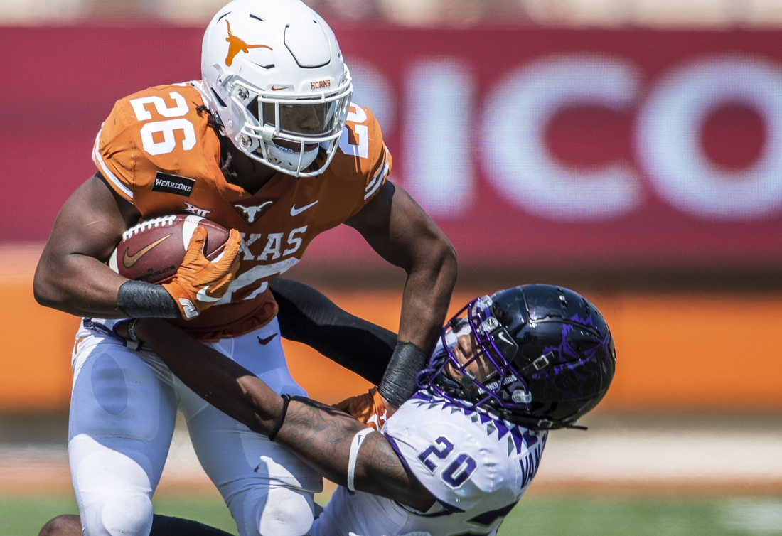 Oct 3, 2020; Austin, TX, USA; Texas Longhorns running back Keaontay Ingram (26) stiff arms TCU Horned Frogs safety La'Kendrick Van Zandt (20) in the 4th quarter in a NCAA college football game  at Darrell K Royal-Texas Memorial Stadium. Mandatory Credit: Ricardo B. Brazziell-USA TODAY Sports