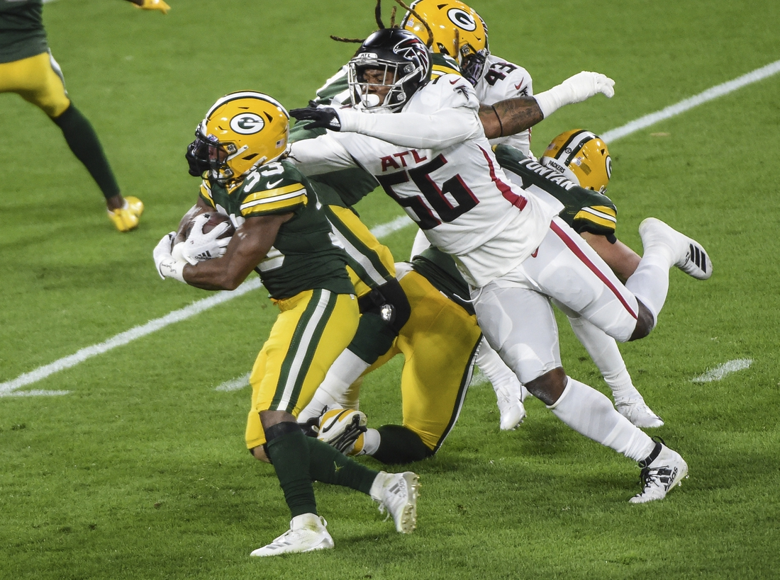 Oct 5, 2020; Green Bay, Wisconsin, USA;  Atlanta Falcons defensive end Dante Fowler Jr. (56) tries to tackle Green Bay Packers running back Aaron Jones (33) in the first quarter at Lambeau Field. Mandatory Credit: Benny Sieu-USA TODAY Sports