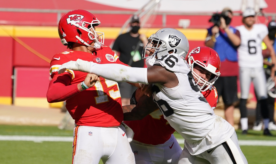 Oct 11, 2020; Kansas City, Missouri, USA; Kansas City Chiefs quarterback Patrick Mahomes (15) is hit by Las Vegas Raiders defensive end Clelin Ferrell (96) while throwing during the second half at Arrowhead Stadium. Mandatory Credit: Denny Medley-USA TODAY Sports