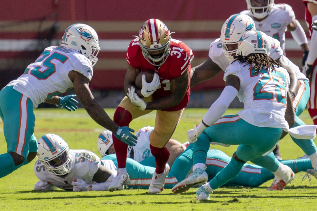 October 11, 2020; Santa Clara, California, USA; San Francisco 49ers running back Raheem Mostert (31) is tackled by Miami Dolphins cornerback Xavien Howard (25) and strong safety Bobby McCain (28) during the second quarter at Levi's Stadium. Mandatory Credit: Kyle Terada-USA TODAY Sports