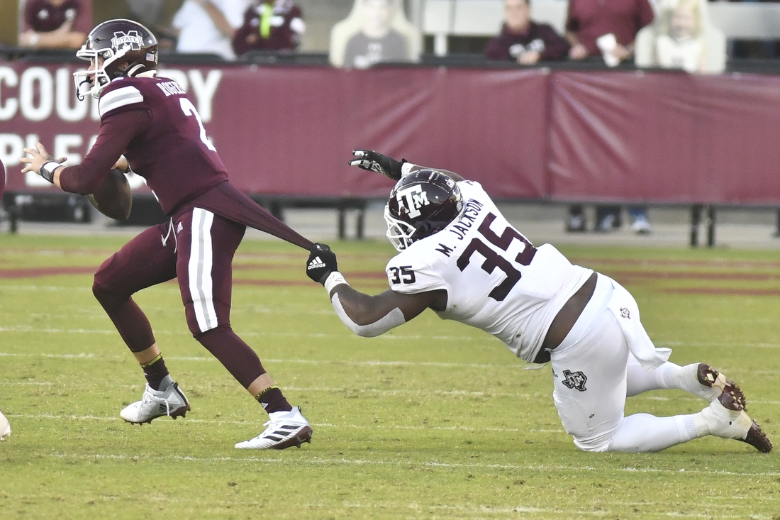Oct 17, 2020; Starkville, Mississippi, USA;  Mississippi State Bulldogs quarterback Will Rogers (2) attempts to break the tackle of Texas A&M Aggies defensive lineman McKinnley Jackson (35) during the fourth quarter at Davis Wade Stadium at Scott Field. Mandatory Credit: Matt Bush-USA TODAY Sports