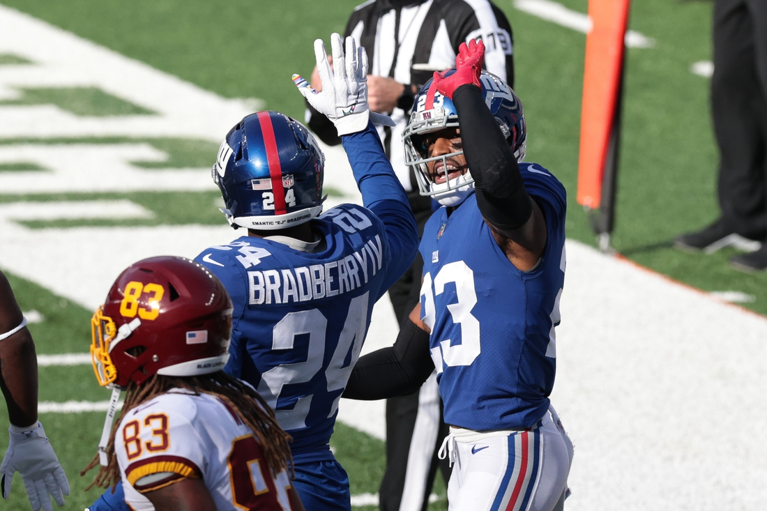 Oct 18, 2020; East Rutherford, New Jersey, USA; New York Giants cornerback Logan Ryan (23) and cornerback James Bradberry (24) celebrate after a defensive stop in front of Washington Football Team wide receiver Isaiah Wright (83) during the second half at MetLife Stadium. Mandatory Credit: Vincent Carchietta-USA TODAY Sports