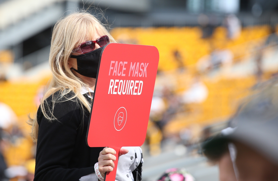 Oct 18, 2020; Pittsburgh, Pennsylvania, USA;  An usher holds a sign as a  reminder of COVID-19 restrictions in place for fans during the game between the Cleveland Browns and the Pittsburgh Steelers at Heinz Field. Pittsburgh won 38-7. Mandatory Credit: Charles LeClaire-USA TODAY Sports