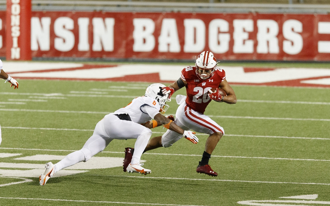 Oct 23, 2020; Madison, Wisconsin, USA;  Wisconsin Badgers running back Isaac Guerendo (20) rushes with the football as Illinois Fighting Illini defensive back Tony Adams (6) defends during the fourth quarter at Camp Randall Stadium. Mandatory Credit: Jeff Hanisch-USA TODAY Sports