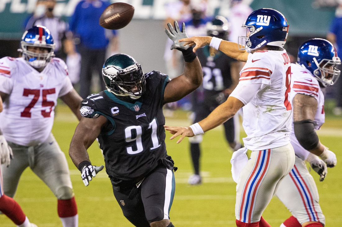 Oct 22, 2020; Philadelphia, Pennsylvania, USA; New York Giants quarterback Daniel Jones (8) attempts a pass in front of the rush of Philadelphia Eagles defensive tackle Fletcher Cox (91) during the fourth quarter at Lincoln Financial Field. Mandatory Credit: Bill Streicher-USA TODAY Sports
