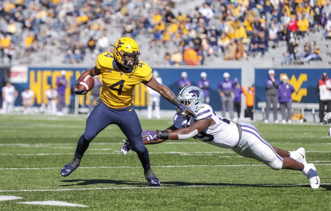 Oct 31, 2020; Morgantown, West Virginia, USA; West Virginia Mountaineers running back Leddie Brown (4) shakes a tackle and runs for a touchdown during the second quarter against the Kansas State Wildcats at Mountaineer Field at Milan Puskar Stadium. Mandatory Credit: Ben Queen-USA TODAY Sports