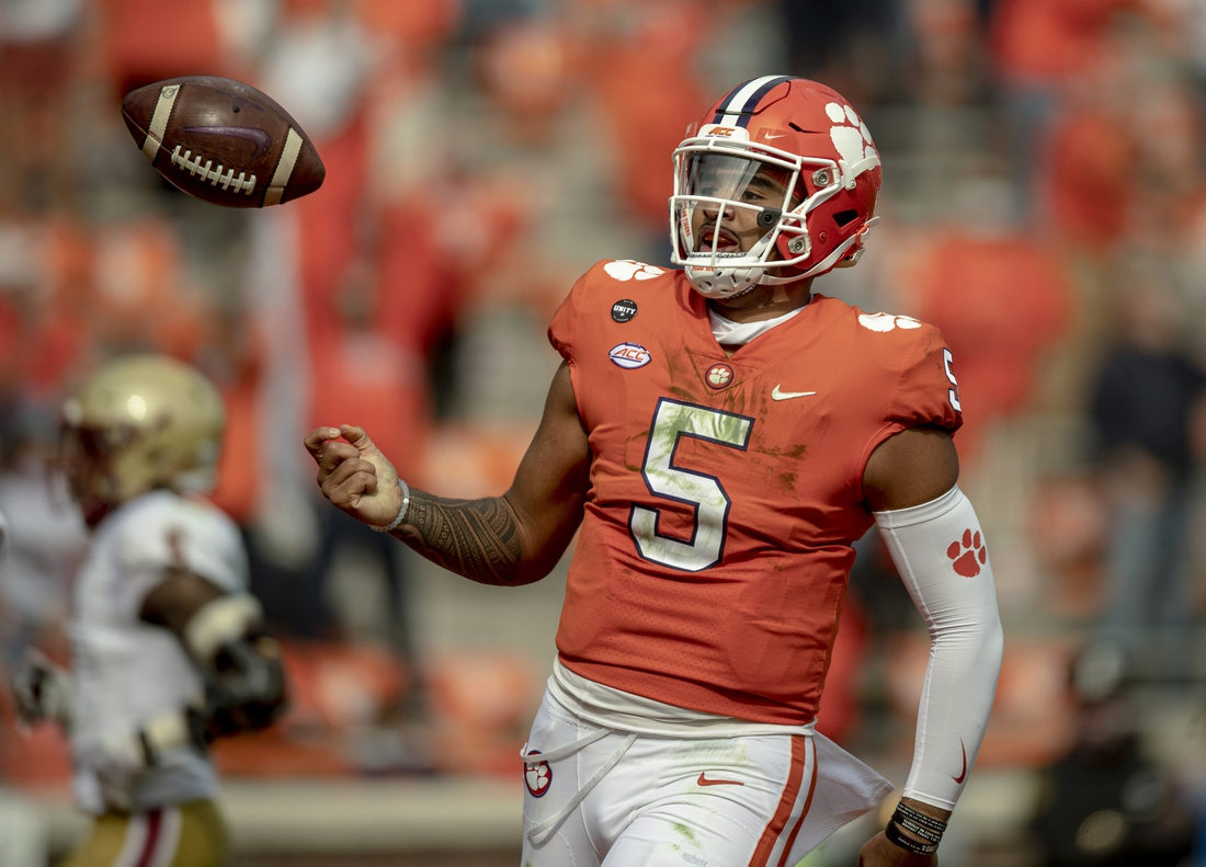 Oct 31, 2020; Clemson, South Carolina, USA; Clemson Tigers quarterback D.J. Uiagalelei (5) returns the ball to a referee after a 30-yard run for a touchdown against the Boston College Eagles during the third quarter at Memorial Stadium. Mandatory Credit: Josh Morgan-USA TODAY Sports