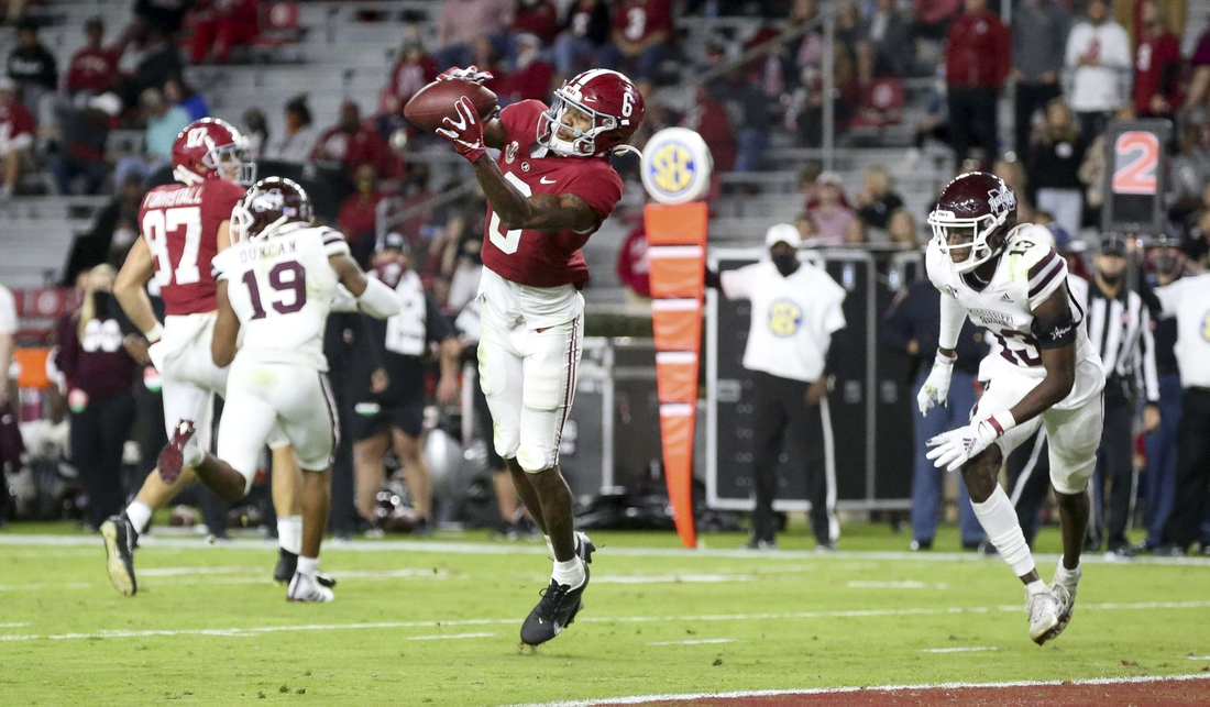 Oct 31, 2020; Tuscaloosa, Alabama, USA;  Alabama wide receiver DeVonta Smith (6) catches a touchdown pass with Mississippi State cornerback Emmanuel Forbes (13) defending at Bryant-Denny Stadium. Mandatory Credit: Gary Cosby Jr/The Tuscaloosa News via USA TODAY Sports