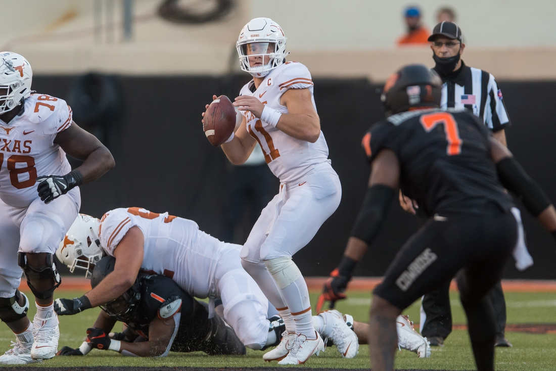 Oct 31, 2020; Stillwater, Oklahoma, USA;  Texas Longhorns quarterback Sam Ehlinger (11) looks for an open receiver against the Oklahoma State Cowboys during the third quarter at Boone Pickens Stadium. Mandatory Credit: Brett Rojo-USA TODAY Sports